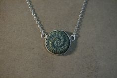 A necklace designed with a hand made bezel with a setting of an old button.