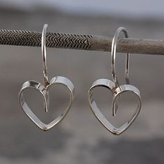 A flat sterling silver wire is carefully and creatively fashioned into the shape of a heart and cleverly suspended from a sterling hook. #Otisjaxon #Jewellery #heart #Women #Giftforher #Accessories