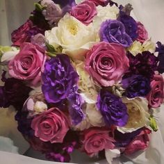 Bridal bouquet in shades of purple and white with roses, lisianthus, freesia, hydrangeas and garden roses