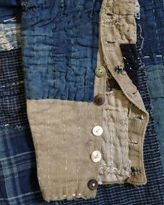 An arrangement of random buttons on the bottom of a Western tailored Japanese boro trouser leg. 1920 or 30s or so.