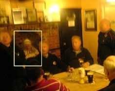 Taken at the New Bell Inn pub in Harwich Essex, England, this photo reportedly shows the ghost of an old woman sitting near the fireplace. According to the original submitter, the men in the pic did not notice the woman at the time of the photograph.