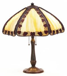 "215.	Handel table lamp, six paneled shade with mottled glass in caramel and cream having a metal overlay design of ivy, original patina, signed on shade, 16""dia. x 20""h, on a bronzed metal base, some minor loss of metal overlay, very good condition 1750-2250"