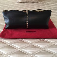 """Extremely RARE! Valentino Garavani rockstud clutch Extremely rare and limited Valentino rockstud clutch. Limited release. Black leather Valentino rockstud clutch with gold-tone hardware, pyramid stud embellishments at center, black leather interior, dual slit pockets at interior walls and flip-lock closure at top. Dimensions: Height 6"""", Width 13"""", Depth 1"""". Excellent used condition. Valentino Bags Clutches & Wristlets"""