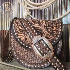 The Saddle Bag - The bold, rugged, modern vintage hand tooled saddle bag. Brown vintage southwest diamond tooled leather throughout front. Entricate rose tooling on flap Cream buck stitching along edges and strap. Gorgeous copper and silver engraved statement buckle on strap. Cowgirl style. Rodeo fashion. Women's Western Wear. Ranch style. Boho Cowgirl. https://savannahsevens.com/products/the-saddle-bag-1