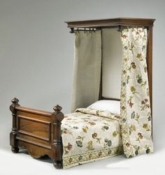 19th Century miniature half tester bed, the tester with a moulded cornice fitted with gilt brass curtain clips, the foot board with turned columns flanking a figured board with applied moulded decoration, raised on turned front feet