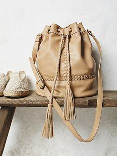 Tempest Bucket Bag | Classic, soft vegan leather bucket bag featuring braided detailing.  Drawstring closure at top with an adjustable long strap.  Inside has one zipper pocket.   *By Free People