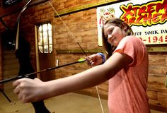 "Ashley Waltersdorf, 11, prepares to shoot at the Extreme Archery indoor range while shooting with her grandmother Miriam Cole on Thursday. Owner Billy Reider says youth interest in the sport is on the rise because of the popularity of the movie ""The Hunger Games."""