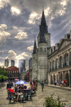 With the modern buildings of New Orleans in the distance, Saint Louis Cathedral (1793) looms over Jackson Square. A variety of goods and services are available at the different tables in Jackson Square, at the table in the foreground of this photo is a Tarot Card Reader where, for a few dollars you can be told your future,