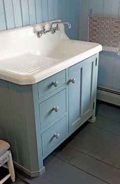 An old kitchen sink makes a nice bath lavatory atop a country cabinet by Crown Point Cabinetry.