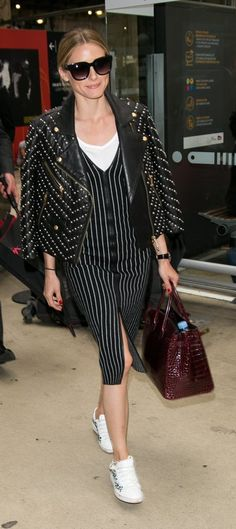 Olivia Palermo in a studded leather jacket, striped dress, and sneakers.