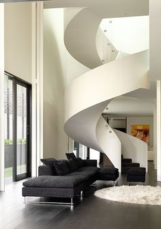 Spiral staircase, dark gray couch, dark wood floors.
