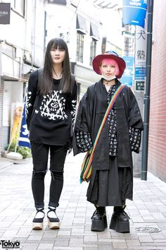 18-year-old students Honoka and Juria on the street in Harajuku. Honoka is wearing a Unif sweatshirt with ripped jeans and Tokyo Bopper platforms. Juria is wearing a kanji print top from HonwakaPappa under a black coat, a black skirt, and Buffalo platforms.