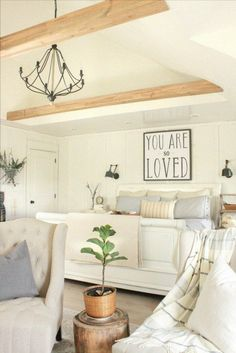 Farmhouse Master Bedroom | ladder night stand | faux beams | farmhouse decor | swing arm lamps | ticking stripe | farmhouse chandelier | farmhouse lighting | neutral decor