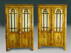 Excepcional y poco común pareja de librerías alacenas/expositores de origen alemán de la alta época Biedermeier* (1825-1830) de preciosas vetas de nogal con 3 columnas frontales ligeramente bombeadas 2 de ellas terminando en patas de la misma forma.