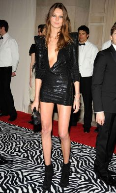 Daria Werbowy in a tiny low cut black dress, showing her slim long model legs.