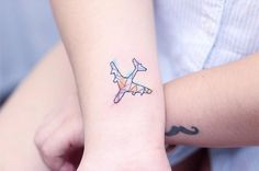 Watercolor/polygon airplane tattoo on the right wrist.
