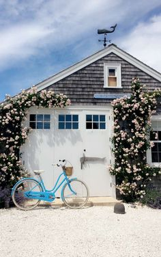 Charming Nantucket-style beach cottage with climbing roses and a bright blue beach cruiser. Charming Nantucket-style beach cottage with climbing roses and a bright blue beach cruiser.