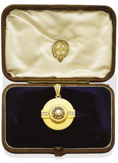 AN ANTIQUE GOLD, PEARL AND DIAMOND LOCKET PENDANT/BROOCH, BY GUSTAV FABERGÉ The circular pendant with applied central plaque set with a pearl and rose-cut diamonds and flanked by lines of split pearls, to the split pearl pendant hoop, with locket opening to the reverse, both pendant and brooch fittings detachable, 4.5 cm long, circa 1860, with marks for 14k gold, in original G. Fabergé fitted brown leather case By Gustav Fabergé, with workmaster's mark W.R. (Cyrillic) for Wilhelm Reimer