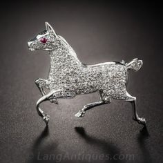 This petite, high-stepping show pony, artfully hand-fabricated in platinum, is thoroughly studded with sparkling white diamonds and a single ruby eye. 1920s-30s vintage. 1 by 7/8 inch.