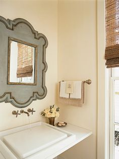 source: My Home Ideas      Eclectic bathroom with gray mirror with gold leaf trim over floating sink and brushed nickel wall-mounted faucet. Bathroom features cream walls and bamboo roman shade over bathroom window.