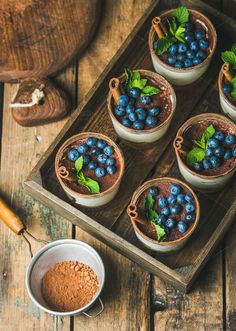 #Homemade Tiramisu dessert  Homemade Tiramisu dessert in glasses with cinnamon mint and fresh blueberries in wooden tray and sieve with cocoa powder over rustic wooden background top view selective focus vertical composition