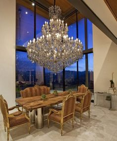 love the oversize chandelier, the juxtaposition of formal chairs with roughhewn table top and corner windows