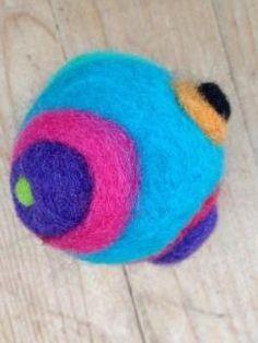 Vilten bal met een belletje erin. Leuk voor een jonge baby: door de bobbels erop rolt hij niet te ver weg Gemaakt van #naaldvilt