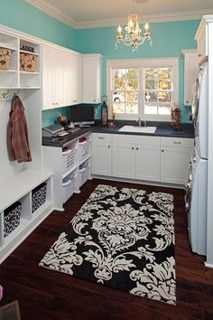 Must have that rug. Laundry room. Turquoise, black and white, chandelier and craftsman trim.