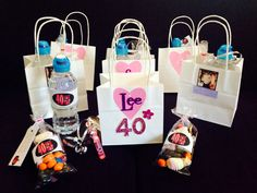 Gift bags for guests at a girls day out. 40th birthday theme. Each bag is personalized with the guests initial & party invite image. Contains emergency water bottle with personalized label, pink bubbles & midnight munchie sweets (40 sweets) also with personalized thank you tags.