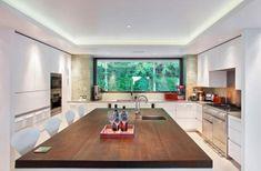 un îlot en bois grand et fonctionnel dans la cuisine blanche