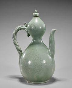 Korean Celadon Glazed Porcelain Ewer, tear-drop form with bulb mouth, moulded rope handle and curved spout; incised floral designs to body; H: 11""