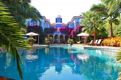 "The vibrantly colored Villa Stella 10,000 square feet on Star Island, 100 feet of waterfront, a dock, and a swimming pool, plus Venetian-stuccoed walls, a 35-foot-tall domed ceiling, and other details ""designed by an Italian sculptor."""