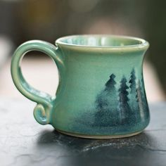 ceramic cafe From her studio in Oregon's scenic Cascade Mountains, artist Dulcie Lindsoe-Johansen hand throws these stout, rustic clay mugs and airbrushes them with a misty forest design Stoneware Mugs, Ceramic Mugs, Ceramic Bowls, Earthenware, Pottery Mugs, Ceramic Pottery, Thrown Pottery, Slab Pottery, Painted Pottery