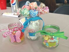 Table Centerpieces for a 1st Birthday Party or Baby-shower.  So easy and affordable to do and they look so cute on tables!! Just take baby food jars and clean them out. Apply stickers on the outside of the jar and tie a ribbon around the top. Fill with your favorite treats like gummy bears and MMs!