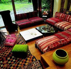 Moroccan-inspired living room setup: sectional bench seating and floor cushions.