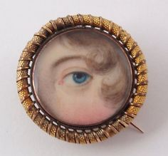 """""""Eye miniatures came into fashion at the end of the 18th century. In France, where eye miniature seems to have originated, the eye as symbol of watchfulness was adopted by the state police for buckles and belts. In Britain it had a role as a love token, with some eye miniatures glistening with a trompe-l'oeil tear, or a diamond set to imitate a tear. Most eye miniatures are unsigned, due to the minuteness of the background, and often the name of the person whose eye is depicted is unknown."""""""