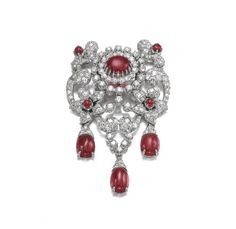 A brooch of swag design, set with cabochon rubies, accented with brilliant- and single-cut diamonds.