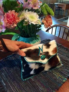 A cowhide wristlet stitched with turquoise leather lace, with turquoise stone and N for Niki. gowestdesigns.us