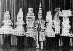 New York's Architects dressed up at the 1931 Beaux-Arts costume ball as the buildings they designed. From left to right: A Stewart Walker as the Fuller Building, Leonard Schultze as the Waldorf-Astoria, Ely Jacques Kahn as the Squibb Building, William Van Alen as the Chrysler, Ralph walker as 1 Wall Street, D.E.Ward as the Metropolitan Tower and Joseph H. Freelander as the museum of New York.