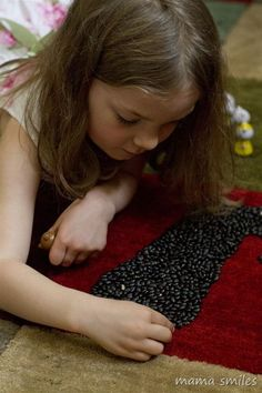 Black bean mosaic art is a fun art activity for kids, and a great way to extend sensory bin materials for older kids!