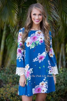 You'll be wishing your toes were in the sand, watching the sunset in this beautiful floral dress! Featuring a beautiful floral fabric with green, light blue, fuchsia, yellow, and white fabric on a deep blue fabric, it simply shines! We also adore the lace eyelets and cuffs on the sleeves, deep v-cutout in back, and criss-cross straps.