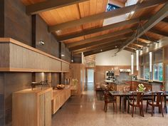 These spacious kitchen and dining spaces feature custom-milled cherry cabinets, vaulted ceilings and terrazzo floors. Large windows keep the space light and bright, while stylish pendant lighting illuminates the rectangular dining table. Weathered steel walls add an industrial touch.