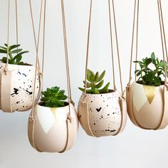 Our hand painted ceramic planters sit in a hand cut leather sling, which can be hung on your wall or in front of a window.