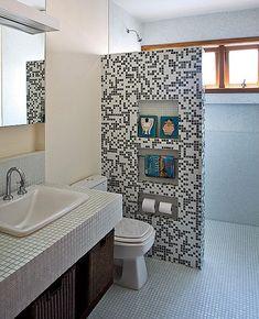 No banheiro, a meia-parede que protege o boxe recebeu pastilhas mescladas e nichos para revisteiros e papel higiênico. Projeto das arquitetas Paula Quatrocchi e Paloma Siqueira