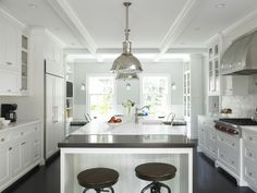 Another nice kitchen with dark hardwood floors, white cabinets, stainless pendants.