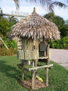Love this complete tiki mailbox with palm fronds.