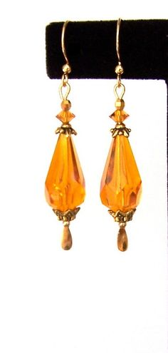 The focal points of these lovely topaz teardrop earrings are faceted topaz vintage lucite beads. They are gorgeous and look like crystal. I adorned them with Swarovski topaz crystals, lovely antiqued gold beadcaps, and little gold mirror beads. The earrings measure about 2 1/4 inches (5.7