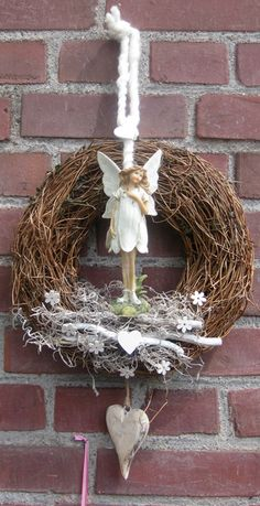 An angel sitting in a nest of white dried flowers . Two hearts and a ribbon dangled below her.  While a white macrame rope hangs above her. The wreathe decorates  a fireplace wall but it can also hang from your door or wall.