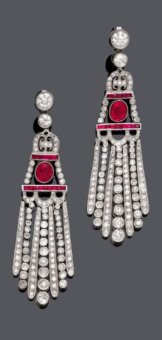 A PAIR OF ART DECO PLATINUM, BURMESE RUBY AND DIAMOND EAR PENDANTS, CIRCA 1920. Each set with an oval Burmese ruby weighing. 1.70 cts, not heated, between two ruby-set lines, four circular-cut diamonds, and suspending a fringe of single- and circular-cut diamonds. 6.3cm long.