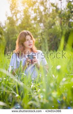 Young beautiful happy woman smiling and enjoying coffee in the green field under morning sunlight.